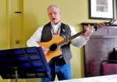 Gray Rinehart opening his author reading session with a song, 2-28