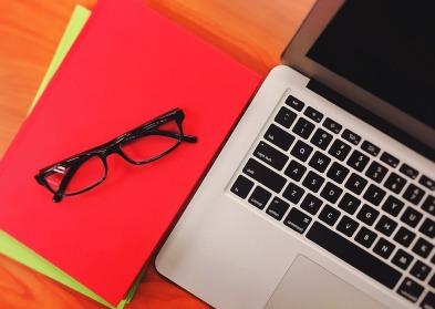 laptop, file folders, eyeglasses
