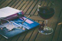 The Author Chronicles, glass of wine, glasses, open book open side down on table